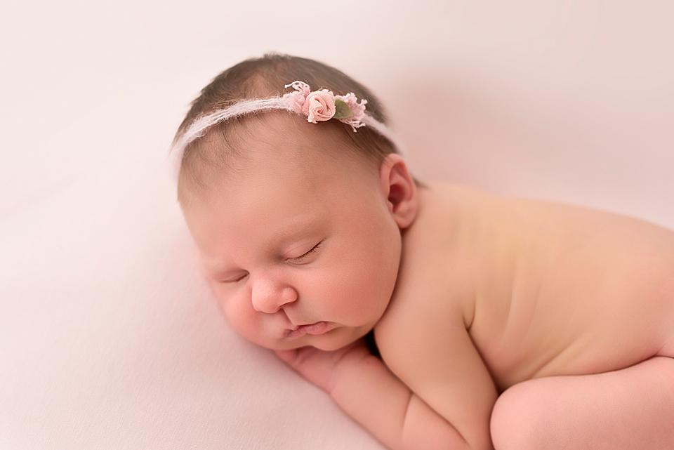 Neugeborenens Mädchen auf rosa decke mit süßem Haarband